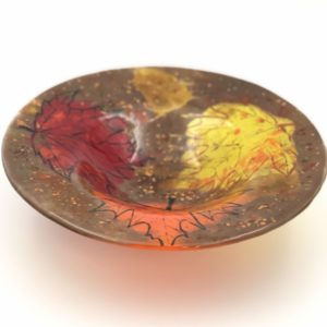 A glass circular bowl with yellow, red nad orange maple leaves and a brown and amber background accented with bronze and black specks