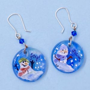 "Two contrasting hand painted snow person earrings on 1"" circles one says ""joy"" one says ""believe"" on blue background with snow"