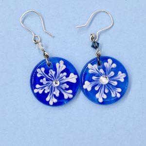 "white snow flake 1"" dangle earrings on a cobalt blue background with crystal bead accents"