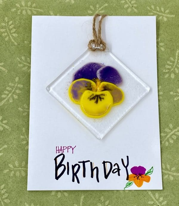 """Card with hand penned """"happy birthday"""" and 3"""" square purple and yellow glass pansy sun catcher attached to the card hanging by the corner"""