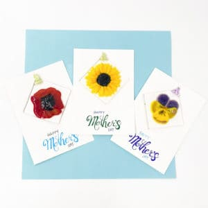 "Three cards that say ""Happy Mother's Day"" each with a glass sun catcher attached. The sun catchers are single blossoms of red peony, yellow sun flower and a purple and yellow pansy"