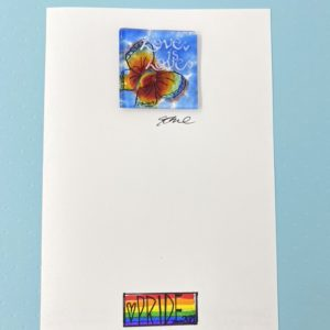 """5x8 rainbow card with a 2x2 square rainbow butterfly glass piece affixed. The butterfly is positioned below the phrase """"Love is Love"""" hand painted in white. The bottom center of the card front has a pride flag with the word Pride and 2020 and a heart."""