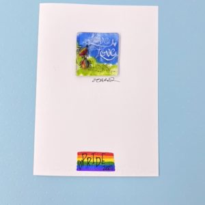 """Two rainbow insects and the words """"Love is Love"""" on a green and blue background in fused glass mounted to the front of a card that has a rainbow flag with the word """"Pride 2020"""" and a heart"""