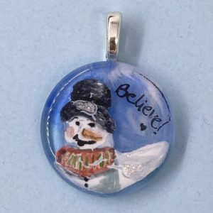 """1"""" circle glass pendant with snow person in a top had and red/green checked vest with the word """"Believe"""" next to it"""