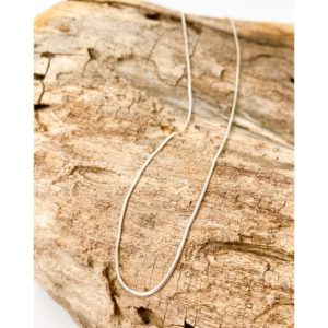 1.2 mm sterling silver snake chain draped over a piece of wood