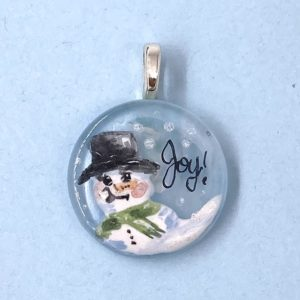 """1"""" enamel painted glass pendant with a snow person in a top hat and green scarf and the word """"Joy"""" written in the sky next to it"""