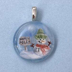 "1"" circle pendant with hand painted snow man wearing a green winter hat and red scarf next to a wooden sign that says ""North Pole"""