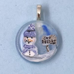 "1"" glass circle pendant with enamel painted snow man in purple knit cap and scarf next to a wooden sign that says ""Ski Resort"""