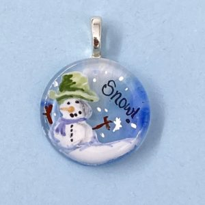 "1"" circle glass pendant with enamel painting of a snow man wearing a green top hat and purple scarf with the word ""Snow"" in the sky next to it"