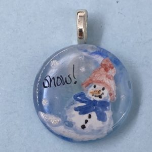 "1"" glass pendant painted with a snow person wearing a red knit hat and blue scarf, ""Snow"" is written in the sky next to the snow person"