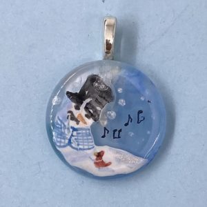 "1"" glass circle pendant with a snow person in a black top hat and blue checked vest singing to a red cardinal at it's base"