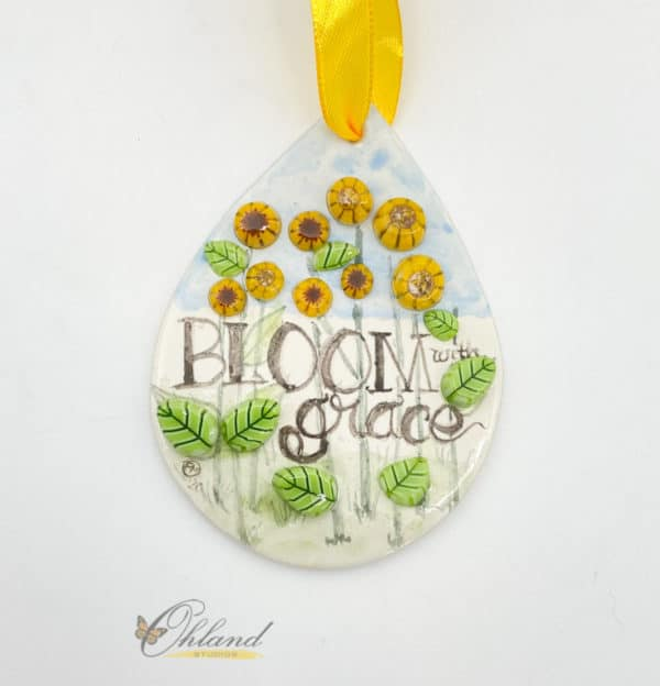 tear drop shaped enameled glass ornament with sunflowers and the saying bloom with grace