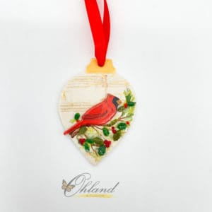 drop shaped ornament with faded music in the background and a bright red cardinal sitting on a holly bush branch