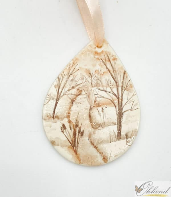 tear drop shaped ornament with a sepia toned winter scene with trees and a stream