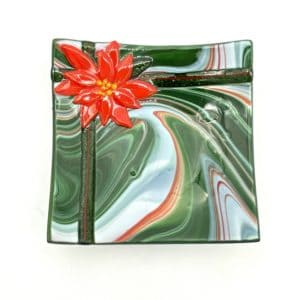 square glass bowl with red green and white swirled glass. Bowl looks like a gift with shiny green glass ribbon and a poinsettia flower accented in 24 carat gold in one corner