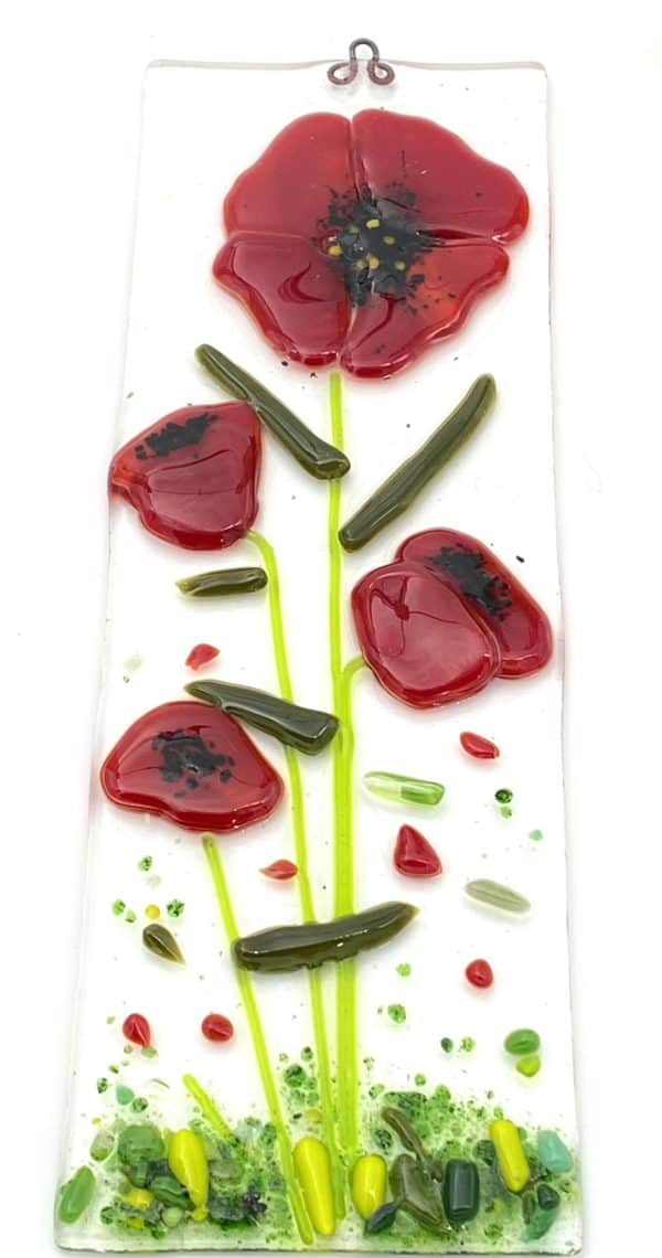 four red poppies with small red bits on a sun catcher