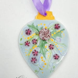purple rose and small flowers with holly leaves on a light blue background christmas ornament
