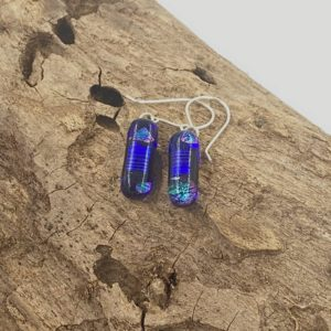 """1/2"""" long with sterling silver ear wire earrings, they are 1/4"""" wide and are dangly the center has a bold very shiny cobalt stripe and at the top and bottom there are super sparkly teal and pink spots"""