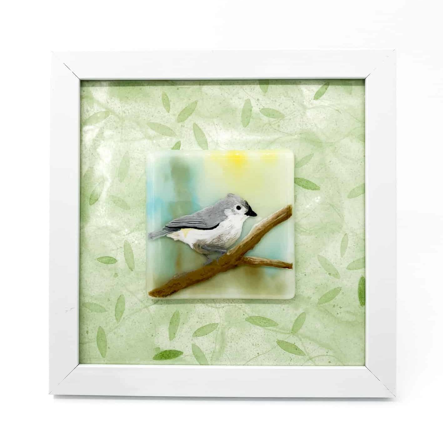 "A grey and white tufted titmouse bird perched on a branch whith a pale yellow, green and blue background. The bird is an enamel painting on a glass tile that is 4x4"". It is framed in a 8x8 frame with a pale green leaf patterned mat."