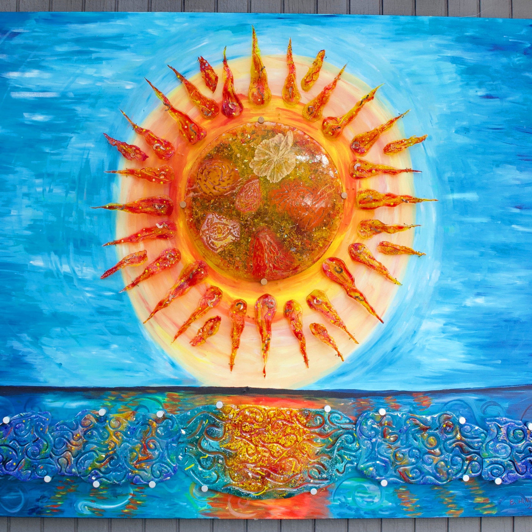"""56""""x72"""" multi media sunset. Large back lit at night sun with individual rays made out of fused glass and mounted on an mdf board painted with a coordinating mural. Water has 5 individual pieces of glass making up the texture. sky and water are in shades of cerulean blue fading to a cobalt blue, sun is orange red and yellow. Sun has images of turtle, palm tree, volcano, hibiscus and fish hook in the center"""